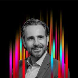 On the middle of a black background is a row of colourful vertical stripes'. In the centre is a black and white profile photo of TEDx speaker Eric Lonergan superimposed on top.