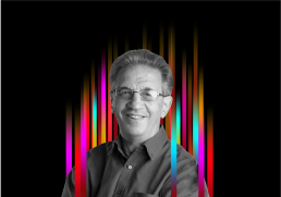 On the middle of a black background is a row of colourful vertical stripes'. In the centre is a black and white profile photo of TEDx speaker Sir Julian Le Grand superimposed on top.