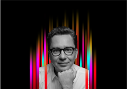 On the middle of a black background is a row of colourful vertical stripes'. In the centre is a black and white profile photo of TEDx speaker Sergey Young superimposed on top.